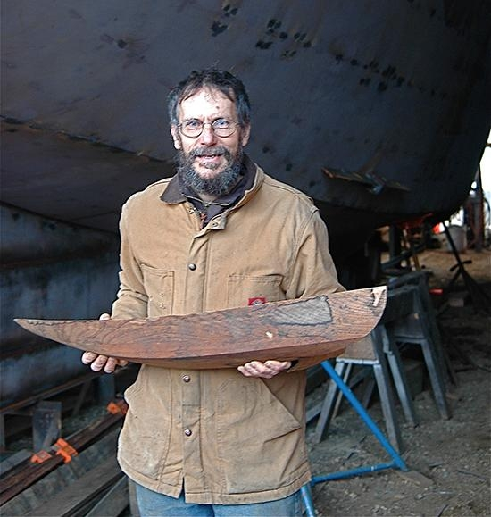 David Stimson stands in front of the partially-completed schooner he was working on when the town shut down his business.