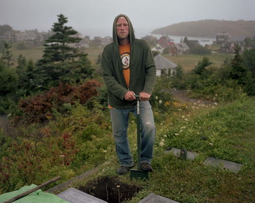 chris rollins, monheagan native, digging grave for summer resident.