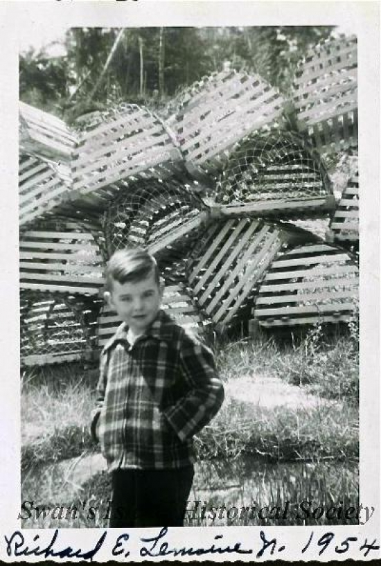 Island kid Richard LeMoine Jr. standing in front of wooden lobster traps, 1954. Courtesy of the Christal Applin Collection.